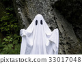 Ghost standing in front of a rock 33017048