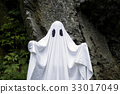 Ghost standing in front of a rock 33017049