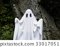 Ghost standing in front of a rock 33017051