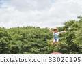 หญิงสาวกำลังเล่นบนแทรมโพลีน 33026195