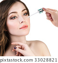Cosmetic oil applying on face of young woman. 33028821