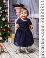 Little girl standing at studio with christmas 33033311