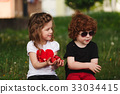 funny boy and girl sharing strawberry 33034415