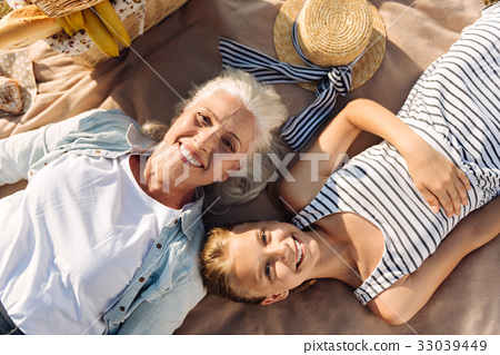 Joyful woman and her granddaughter resting on a 33039449