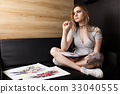 Artist painting in her workshop 33040555