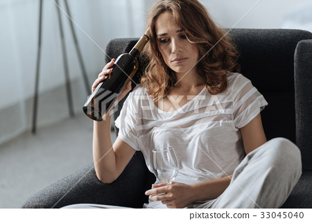 Depressed beautiful woman drinking wine 33045040