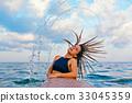 Surfer girl flip wet hair with splashes in air 33045359