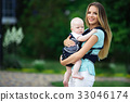 Pretty mother with baby boy in sling walking in 33046174
