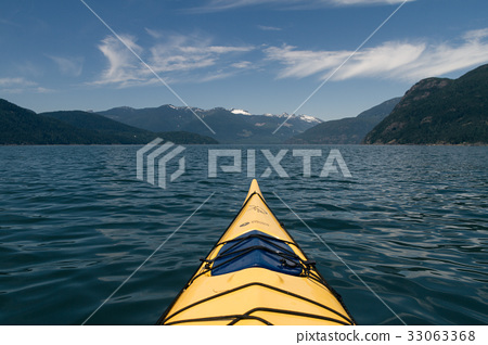 Lone kayaker on water with mountains in background 33063368
