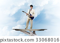 Businessman on metal tray playing electric guitar against blue sky background 33068016