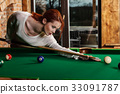 Attractive woman plays game of snooker pool table 33091787