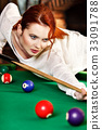 Attractive woman plays game of snooker pool table 33091788