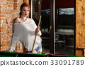Attractive woman plays game of snooker pool table 33091789