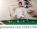 Attractive woman plays game of snooker pool table 33091790