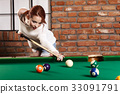 Attractive woman plays game of snooker pool table 33091791