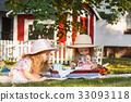 Two little girls sitting on green grass 33093118