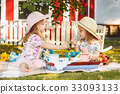 Two little girls sitting on green grass 33093133