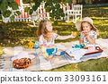 Two little girls sitting on green grass 33093161