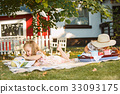 Cute Little Blond Girls Reading Book Outside on 33093175