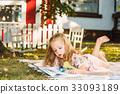 Cute Little Blond Girl Reading Book Outside on 33093189