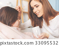 Pretty woman touching forehead of her daughter 33095532