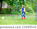 Active cute little kid boy playing soccer and 33099542