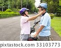 grandmother help grandfather to wear a helmet 33103773