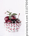 fresh red cherries on a white paper shape 33107904