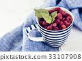 Fresh branch of raspberries in blue stripped mug 33107908