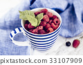 Fresh branch of raspberries in blue stripped mug 33107909