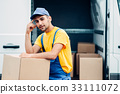Workman or courier holds carton box in hands 33111072