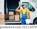 Workman or courier holds carton box in hands 33111079