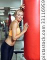 Tired young woman training with punching bag after 33116959
