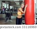 Tired young woman training with punching bag after 33116960