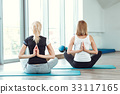 two young women practicing yoga in gym. girl 33117165