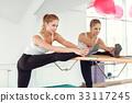 Beautiful slender woman in sportswear stretching 33117245