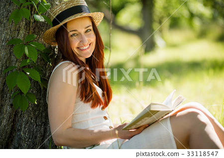 Romantic young lady in straw hat reading a book 33118547