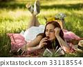 Red haired lady lying on veil on grass eating 33118554