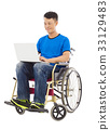 young man sitting on a wheelchair with a laptop 33129483