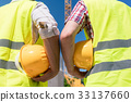 Rear view of hands of workers holding yellow hard 33137660