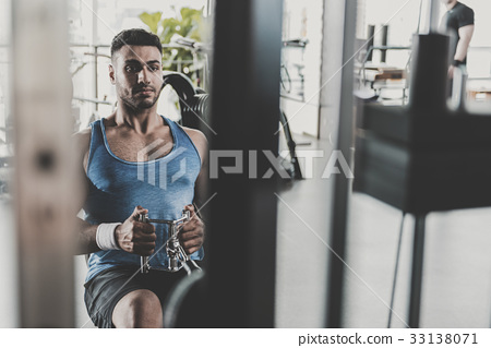 Serene unshaven man exercising in gym 33138071
