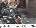 Interested old man on motorcycle 33138287
