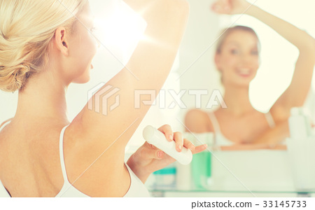 woman with antiperspirant deodorant at bathroom 33145733