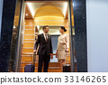 business team with travel bags in hotel elevator 33146265