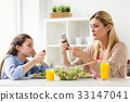 sad girl looking at her mother with smartphone 33147041