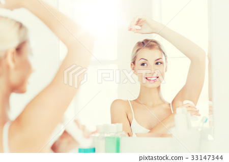 woman with antiperspirant deodorant at bathroom 33147344