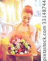 smiling florist woman with bunch at flower shop 33148744