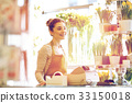 smiling florist woman at flower shop cashbox 33150018