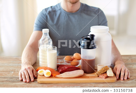 close up of man with food rich in protein on table 33150738