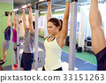 group of people hanging at horizontal bar in gym 33151263